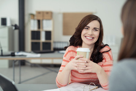 two person: Close up Happy Pretty Woman with Coffee Having a Conversation to her Co-Worker at the Table Inside the Office. Stock Photo