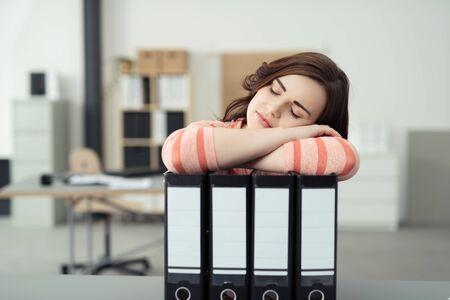 Bored businesswoman asleep on the job lying sleeping with her arms resting on a row of office binders photo