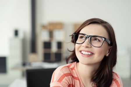 relajado: Mujer joven sonriente llevaba anteojos con marcos y Negro Mirar hacia arriba, como si soñar despierto o que piensa en algo agradable