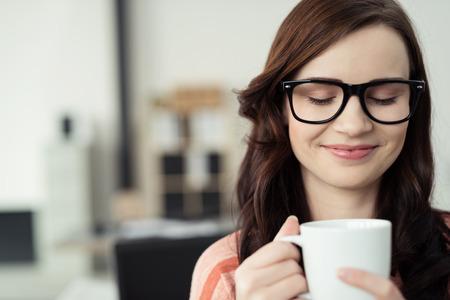 mujer tomando cafe: Primer plano de la joven morena mujer llevaba anteojos con marcos Negro Taza Holding Contiene caliente Bebidas y Inhalar cálido aroma reconfortante