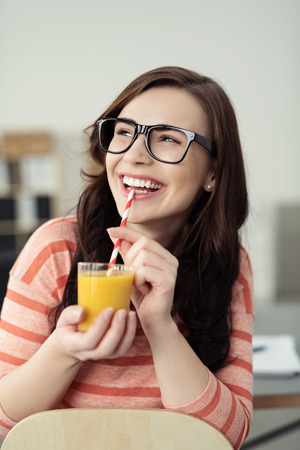 Happy healthy woman drinking orange juice from a glass with a straw beaming as she looks up at something off to the left of the frame Stock Photo