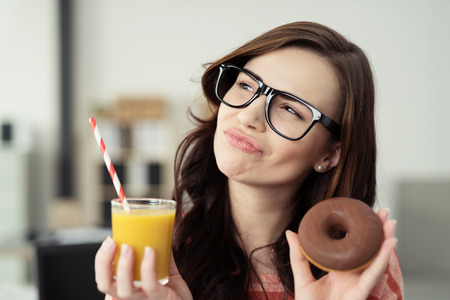 Charismatic young woman wearing glasses deciding between a healthy and unhealthy diet as she holds up a chocolate doughnut an glass of fresh orange juice Banco de Imagens