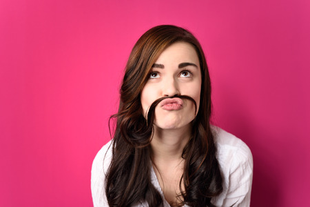 one teenager: Close up Funny Young Woman Putting her Hair Between Nose and Lip and Looking Up. Isolated on a Pink Background.