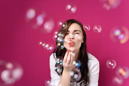 bulles de savon: Ludique parti soufflant des bulles de femme à la caméra comme elle célèbre une occasion ou un anniversaire spécial, sur magenta