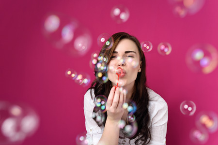 women hips: Playful woman blowing party bubbles at the camera as she celebrates a special occasion or birthday, over magenta