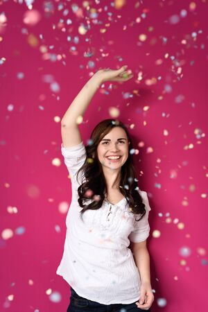 new year eve confetti: Portrait of a Happy Pretty Girl Raising One Arm on a Shower of Confetti While Looking Up. Isolated on a Fuchsia Background.