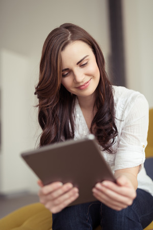 Close up Smiling Pretty Girl with Long Brown Hair, Sitting on Sofa, Holding a Tablet Computer While Looking at the Screen.