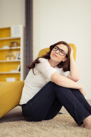 upper floor: Thoughtful Pretty Girl with Glasses Leaning on her Knees While Sitting on the Floor and Looking to the Upper Left of the Frame.