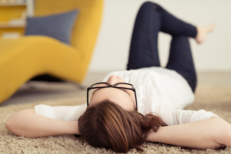 knees bent: Young Woman Wearing Eyeglasses Relaxing on the Floor with Carpet with Hands at the Back her Head and Knees Bent Stock Photo