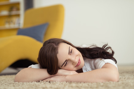 carpet on the floor: Happy woman lying on the carpet daydreaming with her head resting on her folded arms and a smile of pleasure on her face