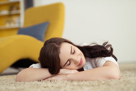 carpet floor: Pretty young woman relaxing on the carpet lying on her stomach with her head on her folded arms with her eyes closed and a smile of pleasure