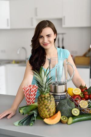 licuadora: Mujer preparando batidos de frutas y verduras sanas felices de pie en su cocina con un montón de ingredientes frescos y una licuadora