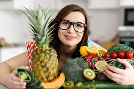 vital: Happy healthy young woman wearing glasses leaning over her kitchen counter with her arms full of fresh cooking ingredients with a variety of fruit and vegetables Stock Photo