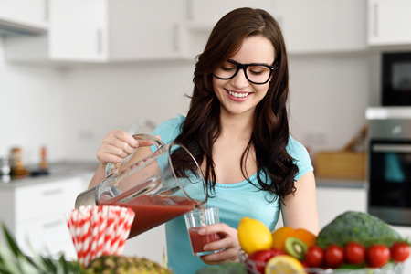 Happy healthy young woman wearing glasses pouring vegetable smoothies freshly made from assorted vegetable ingredients on her kitchen counter