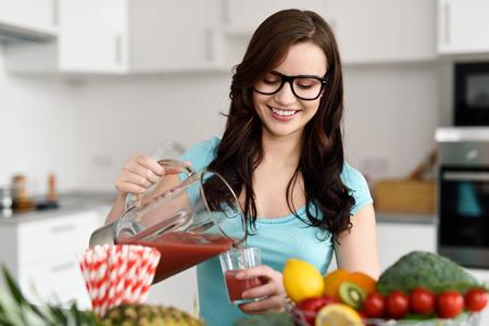 jugos: Mujer llevaba gafas Feliz j�venes sanos que vierten batidos de verduras reci�n hechos con ingredientes vegetales surtidos en su mostrador de la cocina Foto de archivo