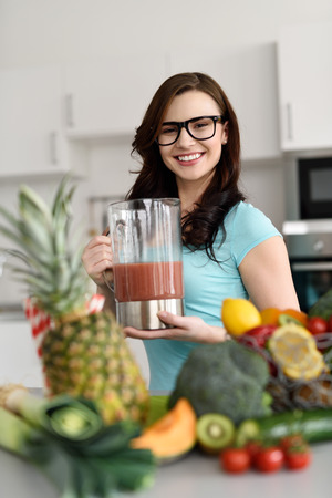 happy healthy woman: Happy healthy woman making smoothies from a variety of fresh fruit and vegetables on her kitchen counter standing holding a blender with fresh prepared beverage as she smiles at the camera