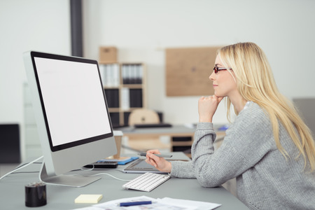 web designing: Young businesswoman wearing glasses sitting at her desk reading her blank white computer screen, profile view in the office