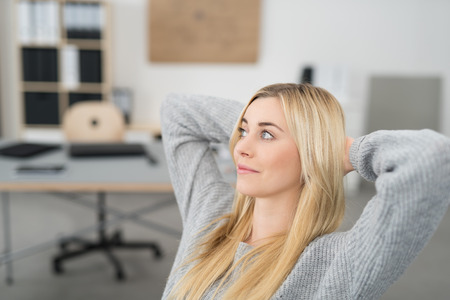 contemplative: Young woman sitting thinking in the office relaxing in her chair with her hands behind her neck staring off into the air with a contemplative expression