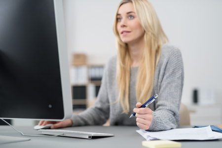 Pretty Blond Office Woman Holding a Ballpoint Pen While Sitting at her Worktable and Facing her Computer Monitor.