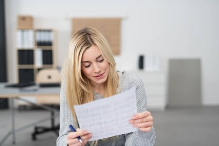 executive courses: Young office worker checking a document holding it in her hands reading through the text with a pen in her hands