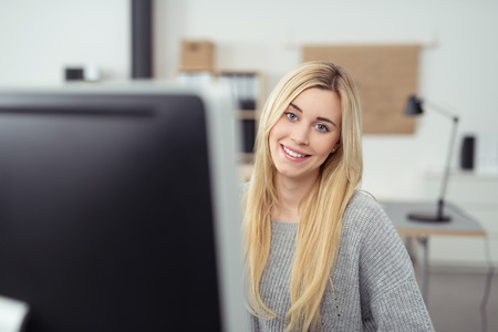 developers: Close up Pretty Blond Woman Sitting at her Desk with Computer Monitor Inside the Office, Looking at Camera.