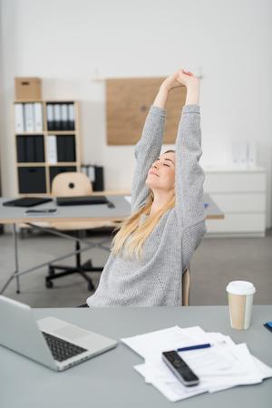 stretching: Joven empresaria se extiende en su escritorio en la oficina con una sonrisa de placer mientras termina su trabajo