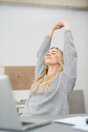 above head: Young businesswoman stretching her arms above her head to relax with a smile of pleasure as she sits at her desk