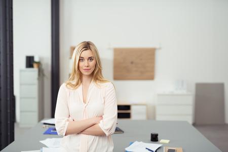 persona de pie: Confiado rubio joven mujer de negocios de pie con los brazos cruzados que se inclina contra la tabla en la Oficina Casual Sala de juntas y mirando a cámara