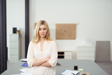 Confident Young Blond Business Woman Standing with Arms Crossed Leaning Against Table in Casual Office Boardroom and Looking at Camera Stock Photo