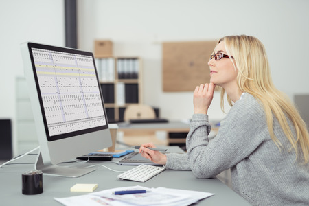 tough woman: Young businesswoman wearing glasses sitting at her desk in the office working on a desktop computer, side view