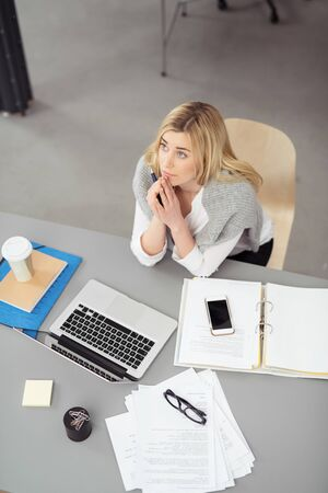 tilted view: Young businesswoman sitting at her desk in the office thinking sitting with clasped hands and her head tilted back staring thoughtfully up into the air, view from above Stock Photo