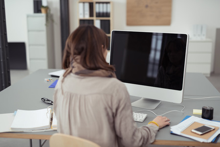 viewed from behind: Young business woman working on her computer in the office viewed from behind with a blank black screen with window reflection