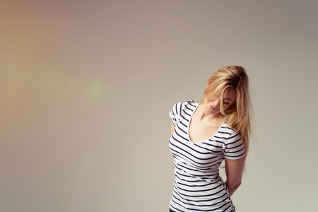 hands behind back: Young Blond Woman Wearing Striped T-Shirt with Hands Behind Back and Leaning to the Side in Studio with Copy Space as seen from Waist Up