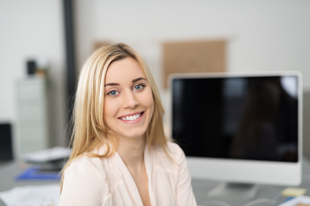 programmer: Close up Optimistic Pretty Blond Girl Sitting at her Worktable and Looking at the Camera with a Toothy Smile.