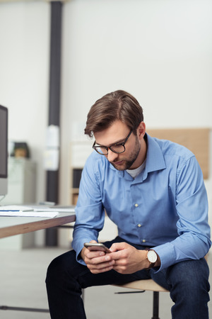 modern businessman: Handsome Young Office Man Using his Mobile Phone While Sitting on a Chair at his Workplace and Leaning on his Knees