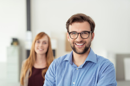 young office workers: Happy Young Businessman Inside the Office, Wearing Blue Polo Shirt with Eyeglasses, Smiling at the Camera In Front his Female Co-worker.