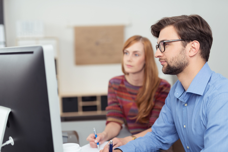 businessman working at his computer: Side view of a bearded young businessman wearing working in the office sitting at his computer with a female colleague behind