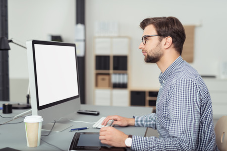 computer monitor: Profile of Serious Young Businessman Wearing Eyeglasses and Checkered Shirt Working on Mac Computer at Desk in Office