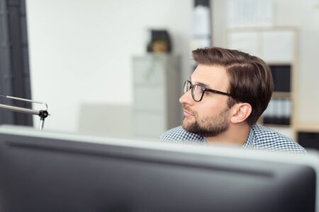 computer monitor: Businessman wearing glasses sitting behind a desktop computer monitor sitting thinking and planning as he stares to the side