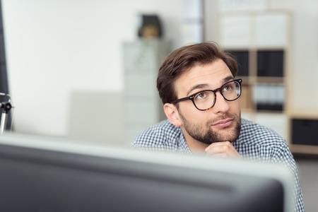 thinking: El hombre de negocios con gafas sentado pensamiento detrás de su monitor de la computadora de escritorio mirando pensativo en el aire con una expresión seria