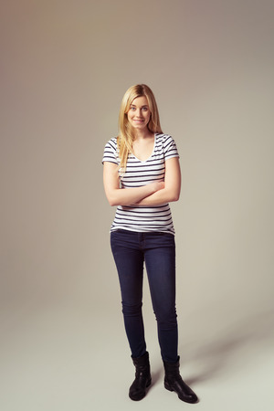 tough woman: Full Length Shot of a Pretty Young Blond Woman in Trendy Outfit Standing Against Brown with Arms Closed. Stock Photo