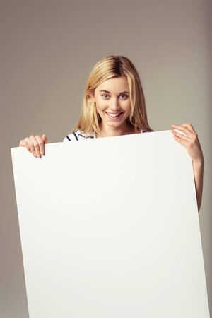 emphasizing: Close up Attractive Young Blond Woman Showing Blank Signboard at the Camera, Emphasizing Copy Space, on a Brown . Stock Photo