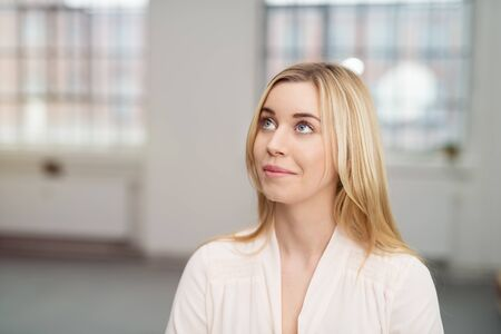 people looking: Portrait of a Thoughtful Pretty Office Woman Looking Up, Captured in Close up. Stock Photo