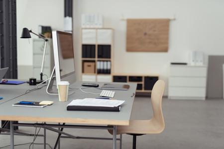 Werktafel met Desktop Computer, kopje koffie, Notes en gadgets Binnen een Office. Stockfoto