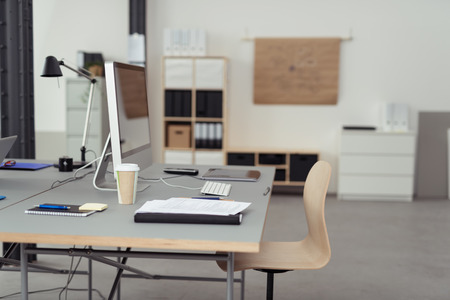 contemporary: Worktable with Desktop Computer, Cup of Coffee, Notes and Gadgets Inside an Office. Stock Photo