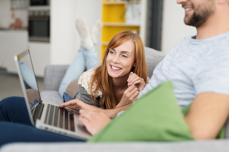 red haired woman: Smiling Red Haired Woman Lying on Sofa Looking On as Man Uses Laptop Computer at Home Stock Photo