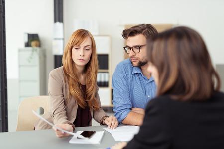 contratos: Reunión joven pareja con su corredor de inversiones discutir un documento con ella durante la presentación, ver sobre el hombro agentes