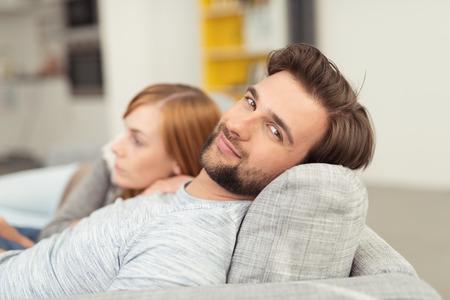 顔の毛を頭のカメラで笑顔で若い男がソファのクッション、彼のそばに背を丸めて女性とリラックスに頼