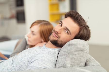 relaxed man: Young Man with Facial Hair Smiling at Camera with Head Leaned Back on Sofa Cushion, Relaxing with Woman Curled Up Beside Him