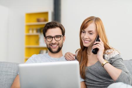 Sonreír Pares que se sientan en el sofá con el ordenador portátil y el teléfono inalámbrico, Encomiendas o compras en línea